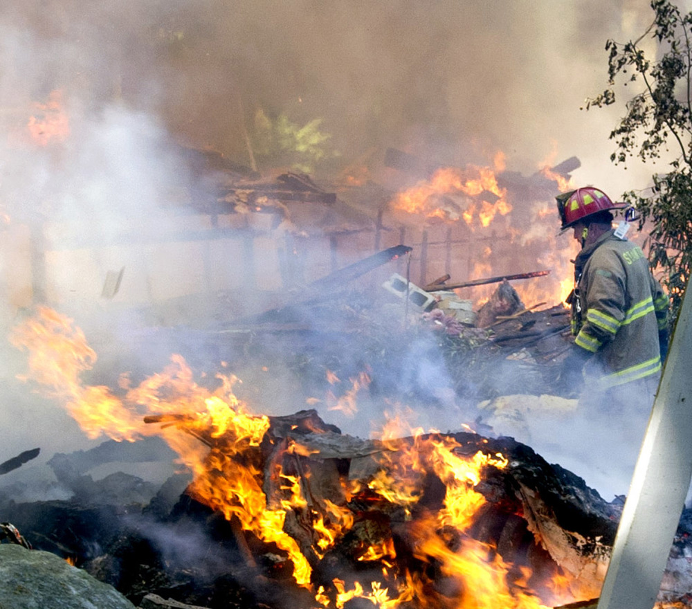 A firefighter walks through the burning rubble of 305 Webbs Hill Road in Stamford, Conn., where the home exploded on Tuesday, Sept. 17, 2013.
