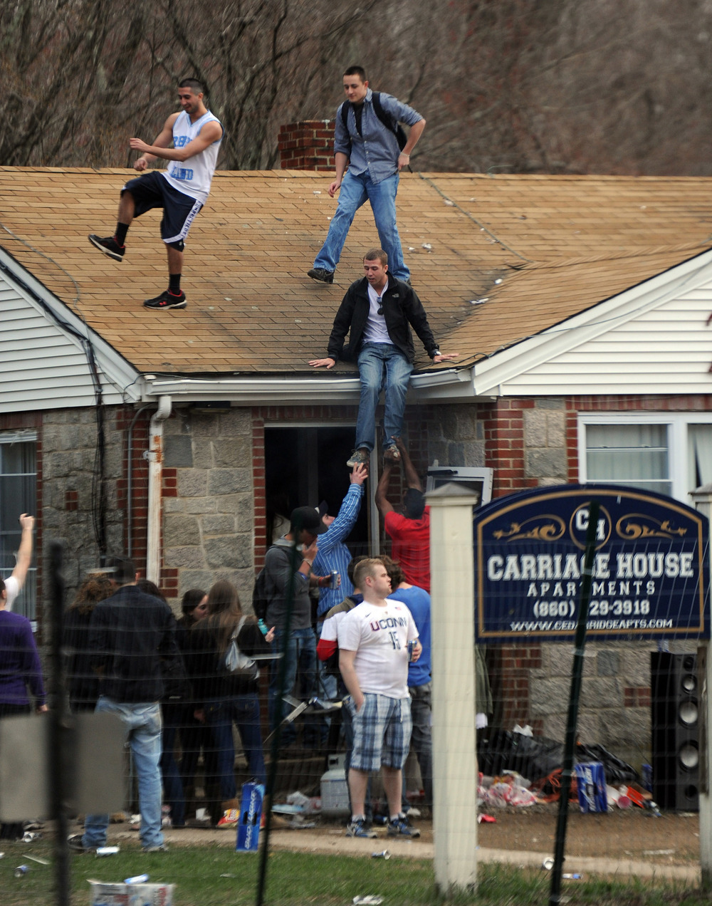 Party-goers stand on the roof of an apartment at the Carriage House Apartments during Spring Weekend at the University of Connecticut on Friday, April 22, 2011.