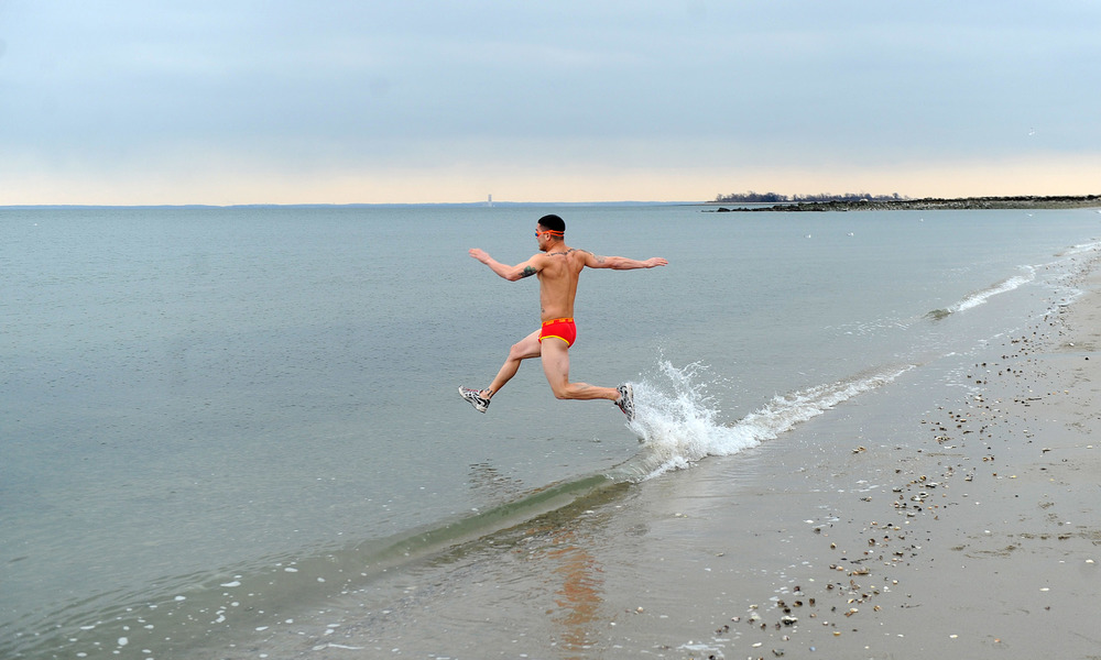 Ken Ildefonso is the first to run into the Long Island Sound at Compo Beach in Westport, Conn., during the Team Mossman Polar Plunge to benefit Save the Children, Tuesday morning, Jan. 1, 2013.