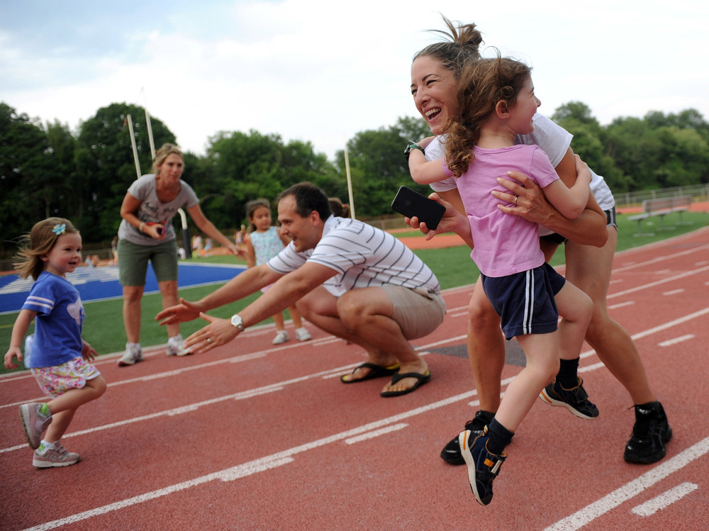 Stephanie Katz picks up her daughter, Nina, as Rob Winslow's daughter, Abby, runs into his arms during the Westport Age Group Track Meet on July 7, 2011.
