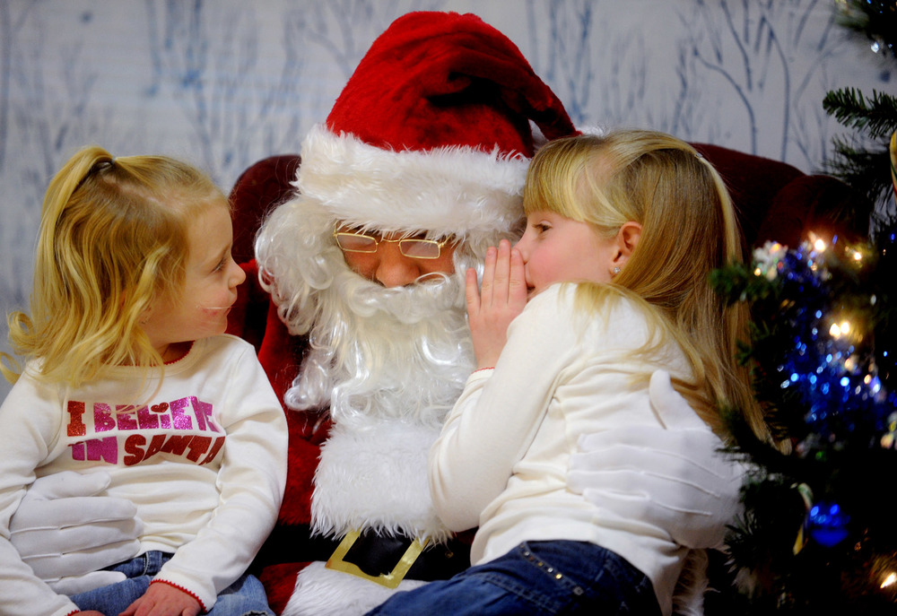 Morgan Sylvia, 6, whispers what she wants for Christmas in Santa's ear as her sister, Darby, 3, listens during the Ludlowe Center for Health & Rehabilitation in Fairfield.
