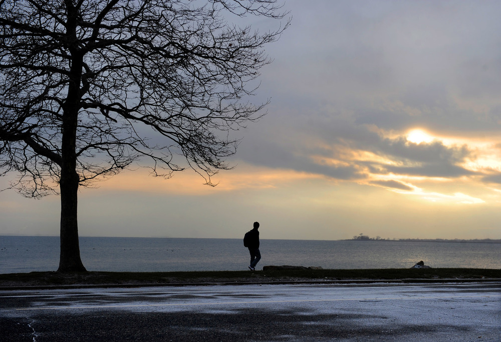 A pedestrian walks along Soundview Drive in Bridgeport on Friday as a light dusting of snow began to cover the street and the sun set on December 10, 2010.