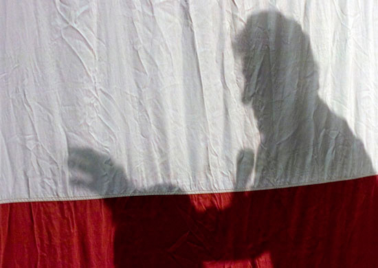 Former President Bill Clinton is silhouetted against the American flag as he speaks about his wife, Senator Hillary Clinton, at Ohio University-Chillicothe on Monday.