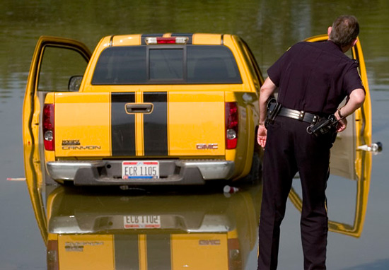 A Chillicothe police officer looks at a GMC Canyon truck that rolled into the Scioto River from a ramp in the Yoctangee Park Annex.