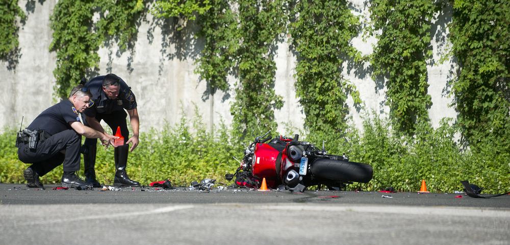 Stamford police officers work at the scene where a motorcycle and Ford Explorer collided in Stamford, Conn., on Friday, June 27, 2014.