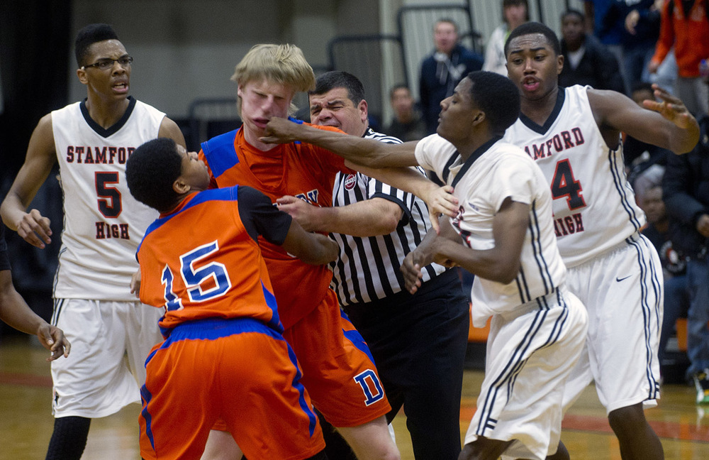 Danbury's Corey Brosz and Stamford's Ancel Nervers fight during Friday's basketball game at Stamford High School on January 17, 2014.
