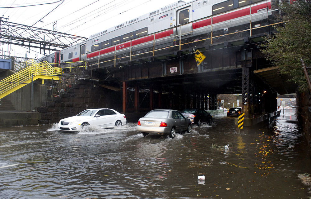 Drivers carefully maneuver through flooding on Elm Street in Stamford, Conn., during heavy rains due to a Nor'easter on Tuesday, December 9, 2014.