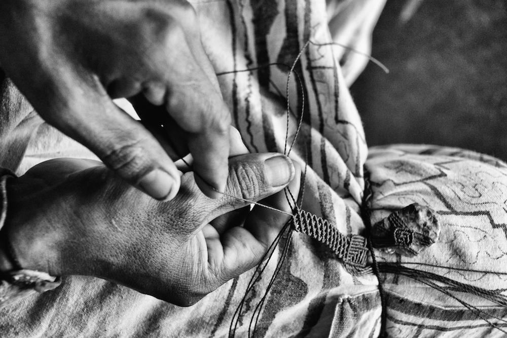 Juan Carlos weaves a bracelet