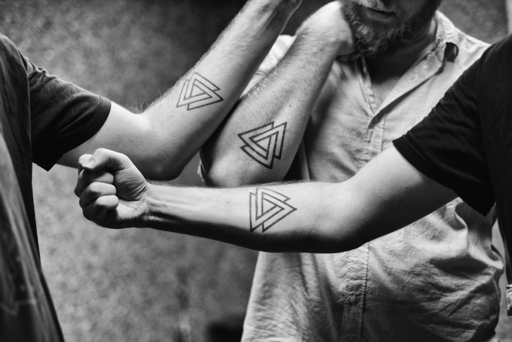 Brothers Pat, Tom and Dan Murphy of Penrose show off their matching tattoos, the symbol of the band