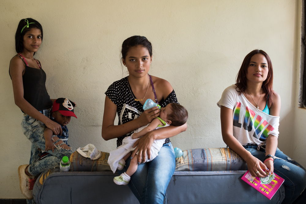 (Left to right) Angie, 17, with her son Samuel, 11 months, Alejandra, 15, with her son Juan José, 3 months, and Dominica wait for class to begin. The girls are studying computer systems in the hopes of having some professional skills to find work.