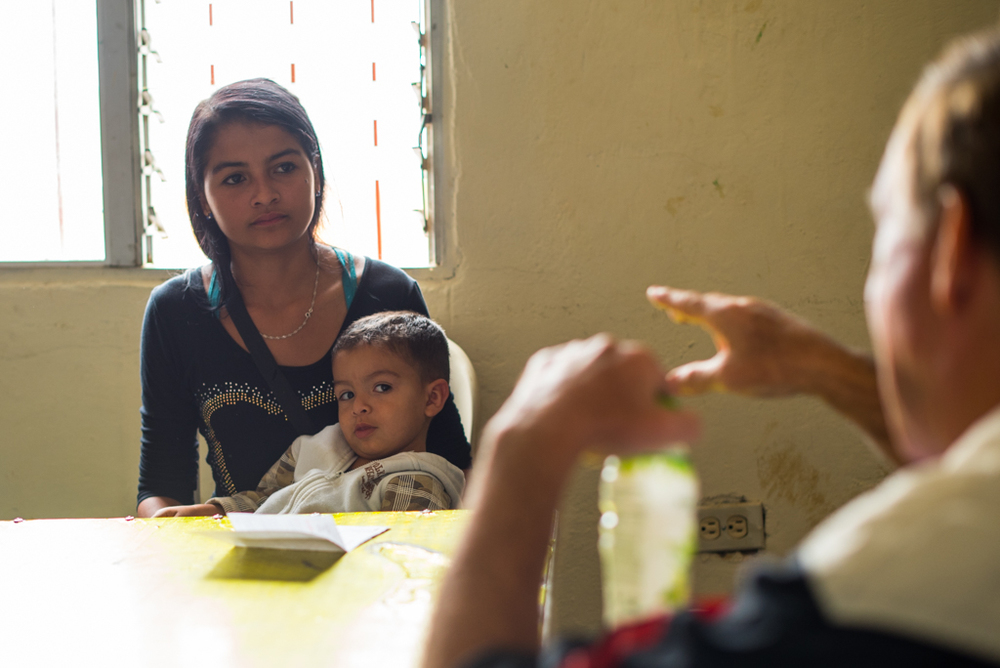 Shirley, 16, and her son Alejandro, 2, listen to the director of a local community foundation. She has come to ask for money to buy Alejandro's baptism outfit which costs 250,000 pesos ($79). She doesn't have the money to pay for the outfit, which is eight times the amount of her monthly rent, but Alejandro cannot be baptized without it. If she doesn't baptize him the government will take him away and put him up for adoption.