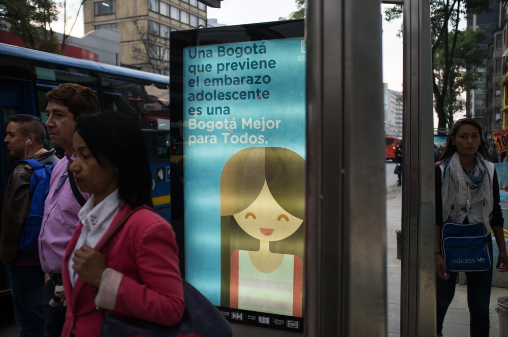 "A sign at a bus stop in Bogotá reads: ""A Bogotá that prevents an adolescent pregnancy is a better Bogotá for everyone."""