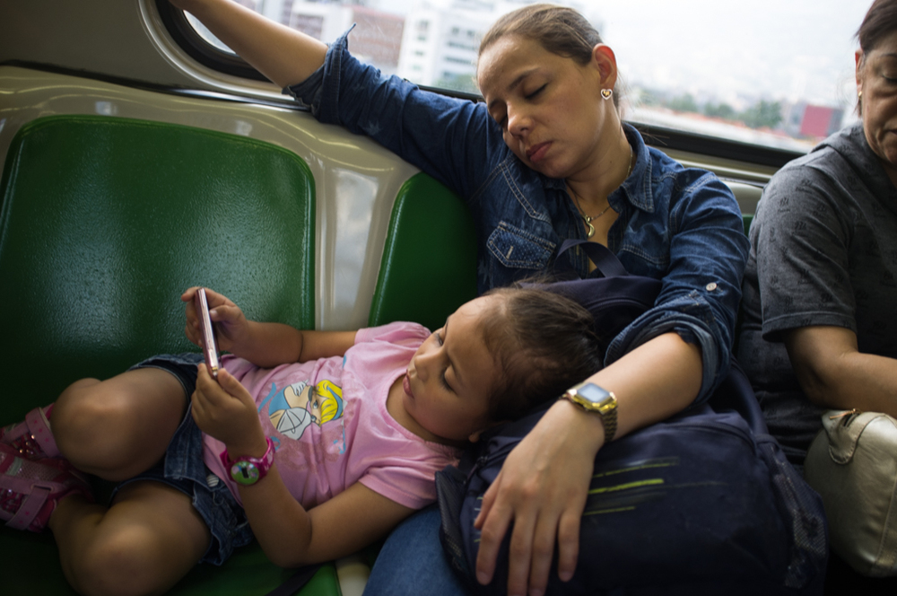 A mother rests on the metro in Medellín