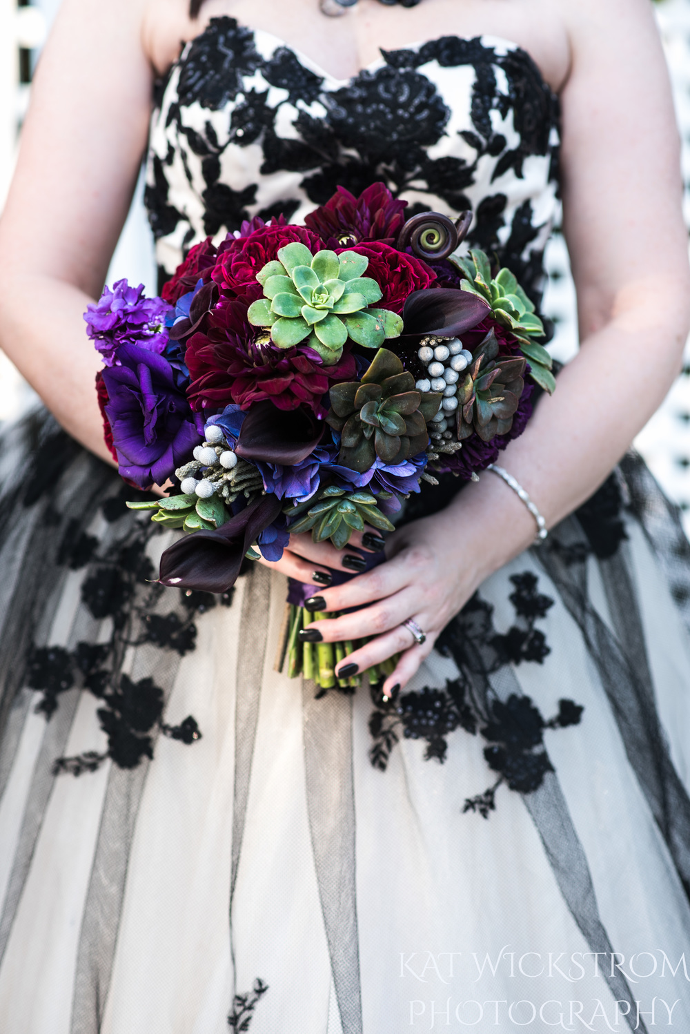 The bridal bouquet had succulents and dark purple flowers. They went perfectly with her black nails and dark theme.