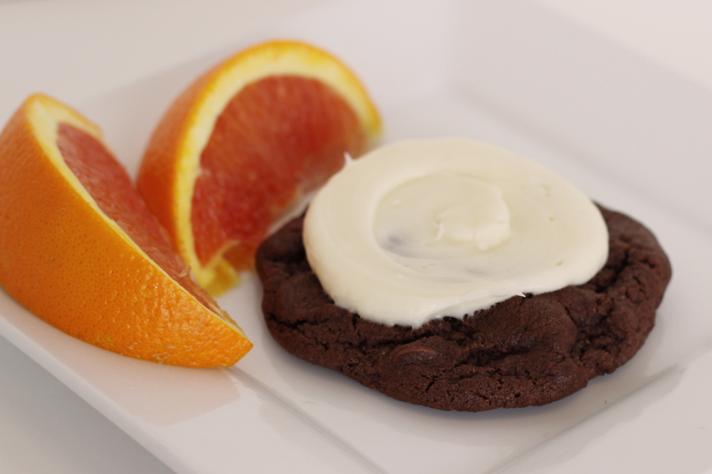 Chocolate Orange Chocolate cookie filled with Callebaut chocolate chips and topped with a fresh orange cream cheese frosting.