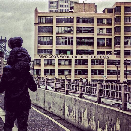 Author Kellen Brandon and his daughter Amiya walking across the Brooklyn Bridge.