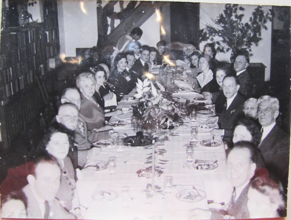 """Christmas dinner in the living room at the Gaard House. The Neergaards hosted many a dinner; one year Coralie Mead Brooke described them as """"….drinks, dinner, decorations, de-lovely."""""""