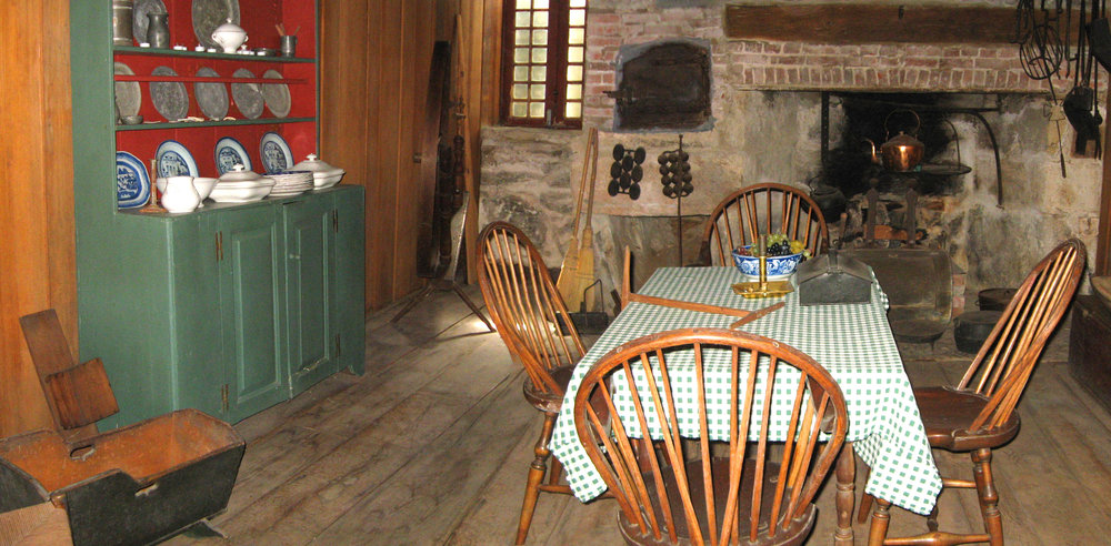 Interior view of the main room in the basement level of the Homestead, with the bread oven in the wall and the main cooking fireplace.
