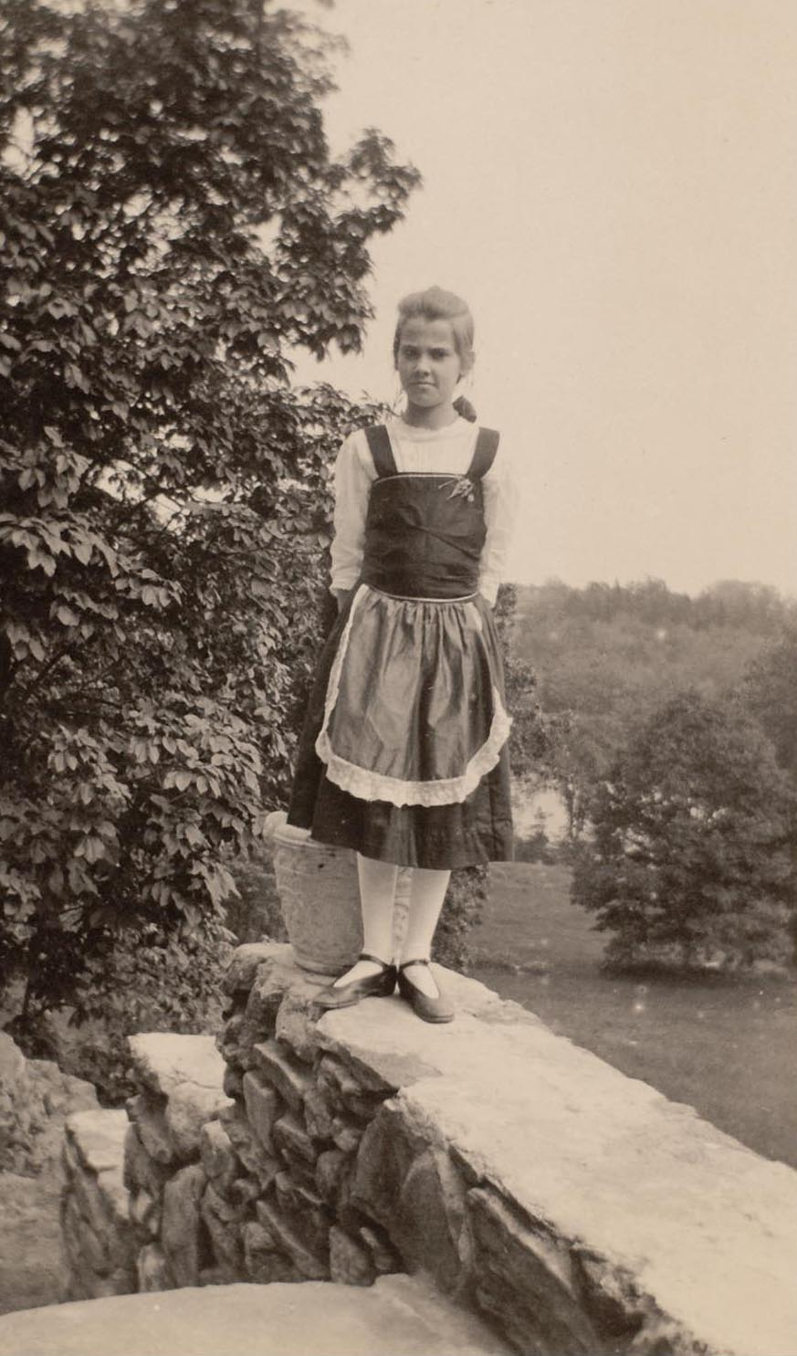 "Sarah ""Sally"" Frances Smith standing on the terrace, probably circa 1915. Lake Waccabuc can be seen behind her."