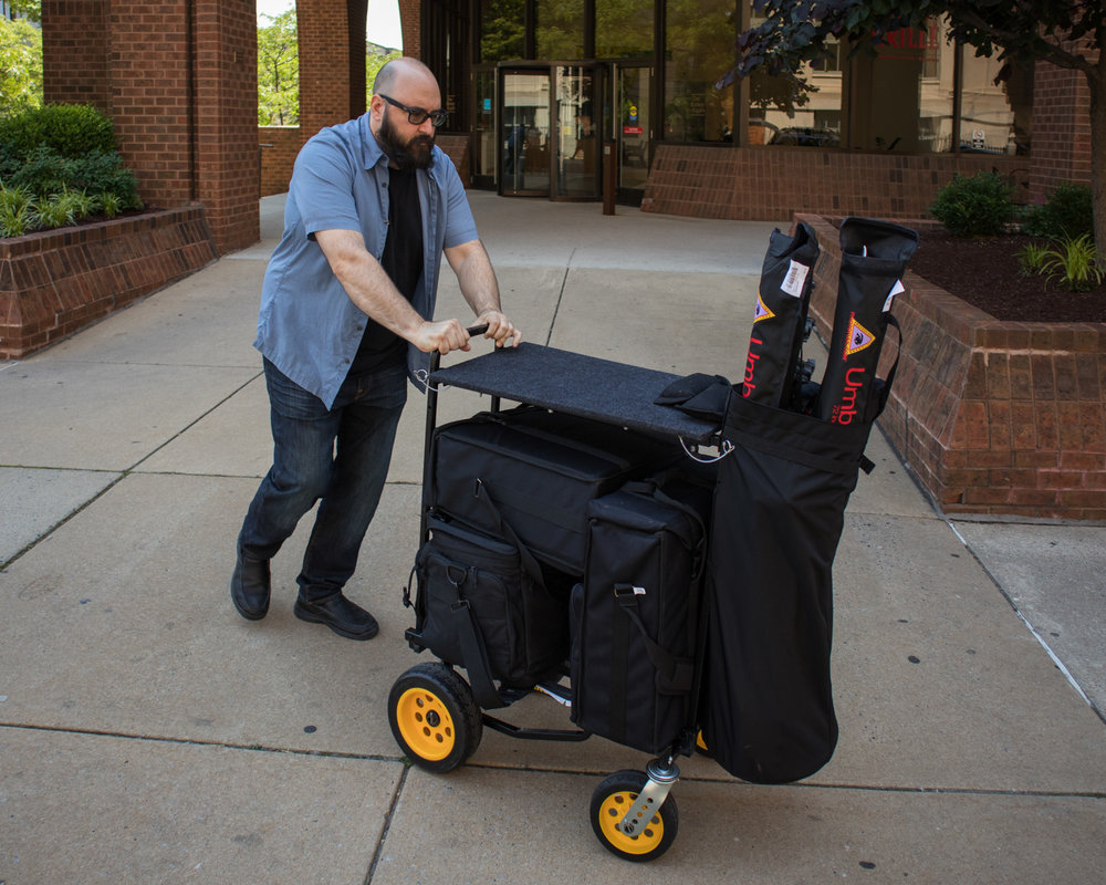 Real estate photographers get to travel light, a duffel or backpack and a tripod. Here is my assist Don with the gear we needed for a simple architectural shoot. We normally need a bit more, I can see just by looking at the cart that we didn't have reflectors and skrims (large sheets of light diffusion material), maybe I am carrying them here.