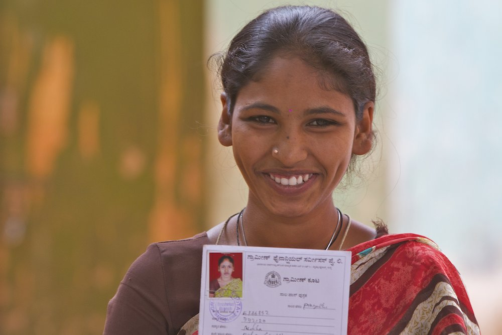 An Indian woman shows her WaterCredit loan card. Photo credit: Water.org