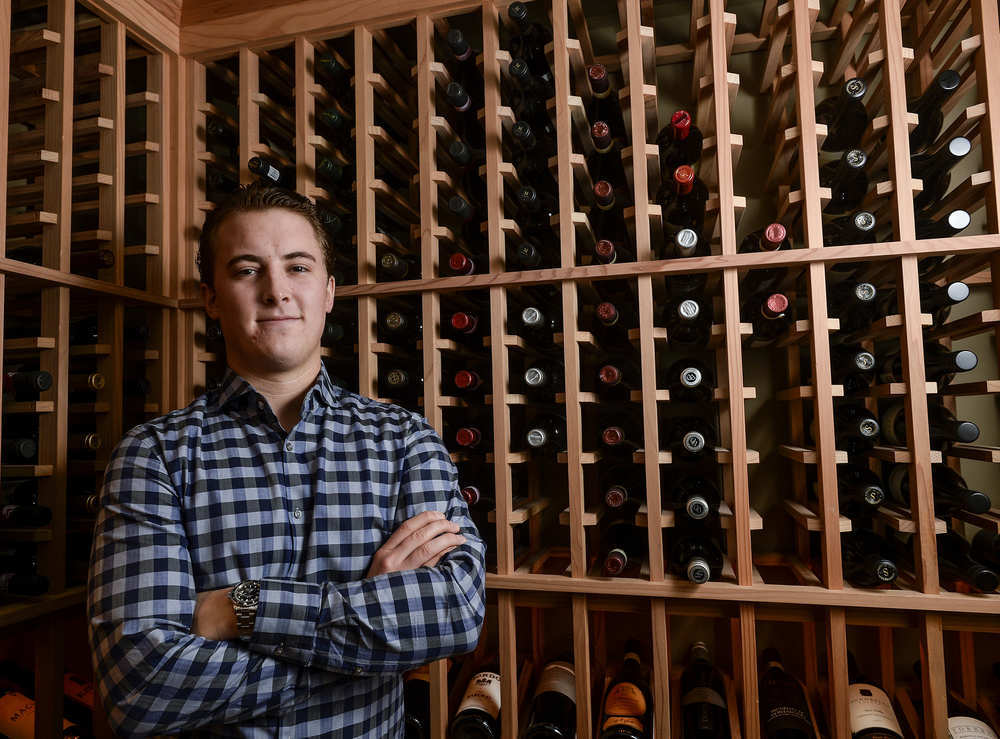 Adam Phillips stands in his wine cellar in his home in Toronto's West end. He shares this cellar with his father who has been teaching him about the fine art of wines. Phillips has been growing his own personal collection over the past few years.
