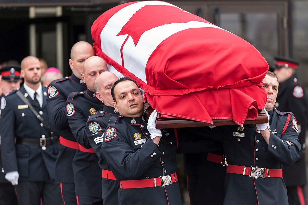 PC Paul Russell, long-time friend of fallen Constable John Zivcic, follows the casket out of the Toronto Congress Centre on December 9, 2013 after a memorial service. Constable Zivcic succumbed to injuries after an accident while responding to a call.