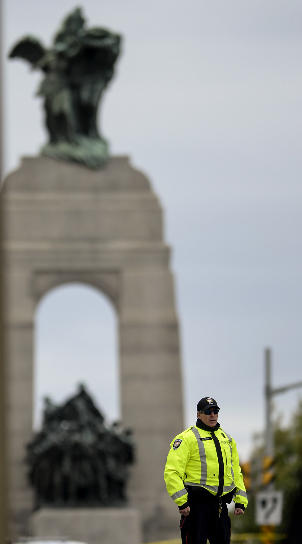 OTTAWA, Ont. (22/10/14) - A police officer stand directing traffic and pedestrians away from the scene of a brazen early morning shooting at the National War Memorial in Ottawa, Ont. on Wednesday Oct. 22, 2014. Photo by Andrew Lahodynskyj