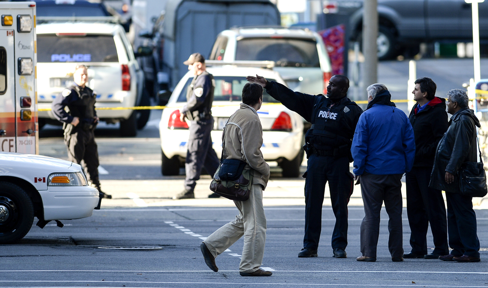 OTTAWA, Ont. (22/10/14) - A police officer directs citizens to a bus stop after they were allowed to leave buildings in the downtown core of Ottawa after a lockdown due to a dead morning shooting. Photo by Andrew Lahodynskyj