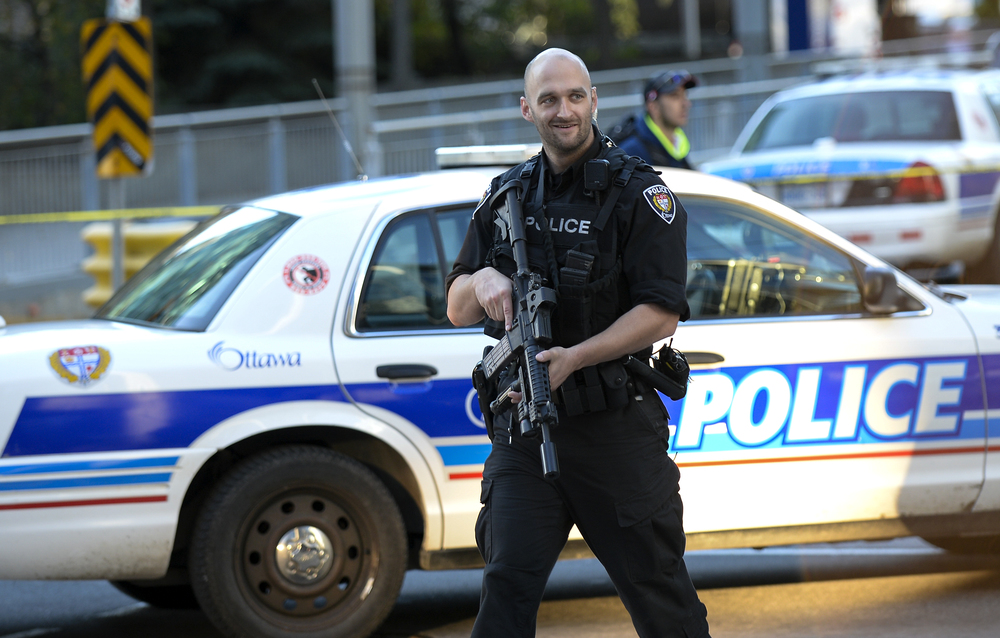 OTTAWA, Ont. (22/10/14) - A heavily armed police officer walks down Metcalfe St in Ottawa, Ont.,  on Wednesday Oct. 22, 2014 after shots were fired at the National War Memorial and at Parliament Hill. A suspect had gunned down a soldier who was standing guard at the tomb of the unknown soldier. Photo by Andrew Lahodynskyj