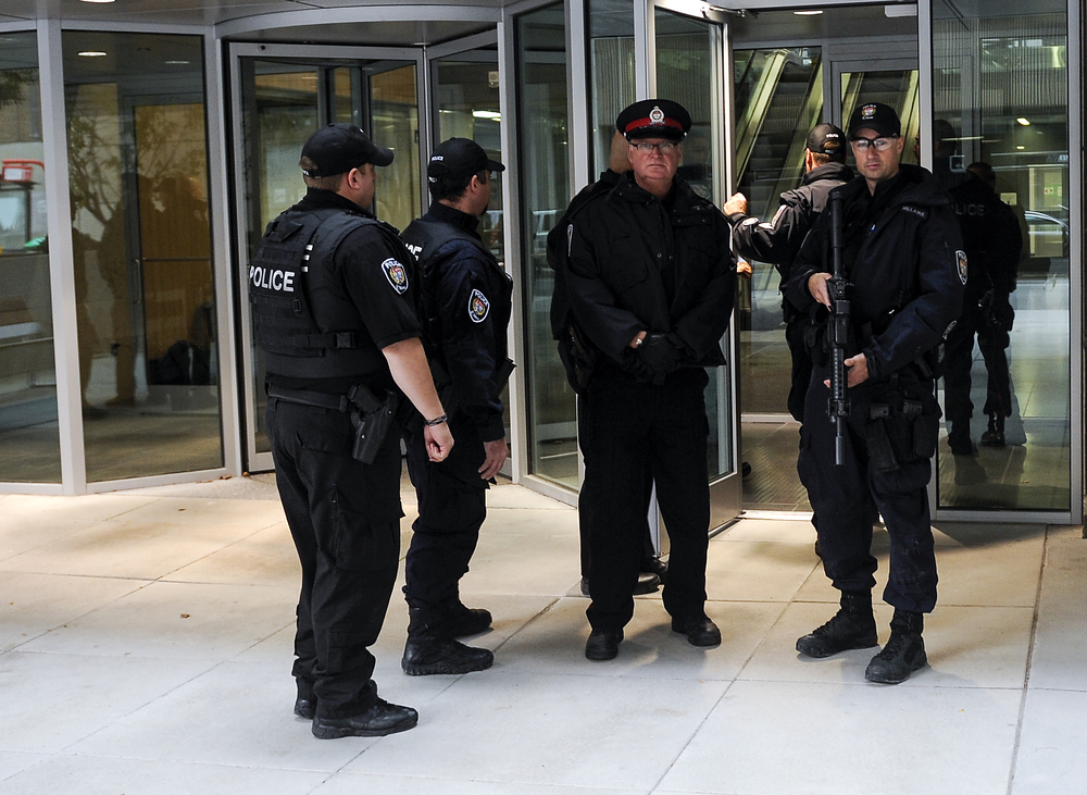 OTTAWA, Ont. (22/10/14) - Armed police make their way into 90 Elgin St government building during an on-going search for a potential secondary shooting in Ottawa, Ont., on Tuesday Oct. 22, 2014. A gunman had opened fire on a solider standing at the National War Memorial around 9:50am then proceeded to storm the Parliament building where lots of gunfire was heard. Photo by Andrew Lahodynskyj