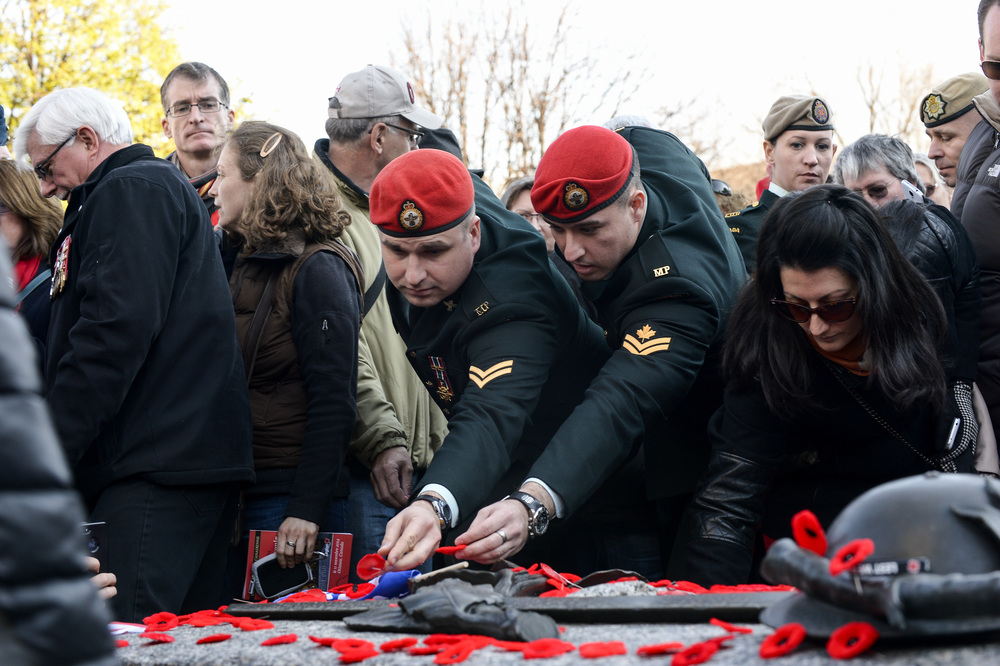 OTTAWA, Ont. (11/11/14) - Two members of the Military Police lay down their poppies on the Tomb of the Unknown Solider at the National War Memorial after a Remembrance Day ceremony in Ottawa on Tuesday Nov. 11, 2014. Photo by Andrew Lahodynskyj/