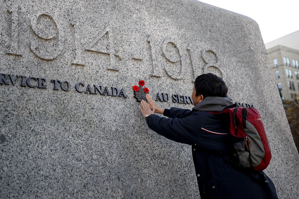 OTTAWA, Ont. (11/11/14) - A woman places her hands on the National War Memorial after placing three poppies around the maple leaf in Ottawa on Tuesday Nov. 11, 2014. Photo by Andrew Lahodynskyj/