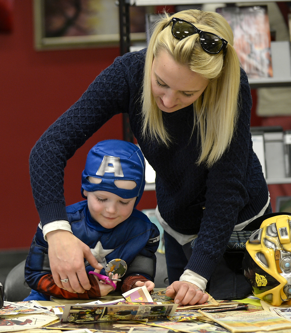 Kylli Richards helps her son Cohen Richards, 3, with constructing a wallet out of comic book pages at the Comic Book Jam held at the downtown branch of the London Public Library on Wednesday March 18, 2015. Organizers said that around 200 kids came out this the fifth annual event this year, which help promote reading and arts. ANDREW LAHODYNSKYJ/ The London Free Press /QMI AGENCY