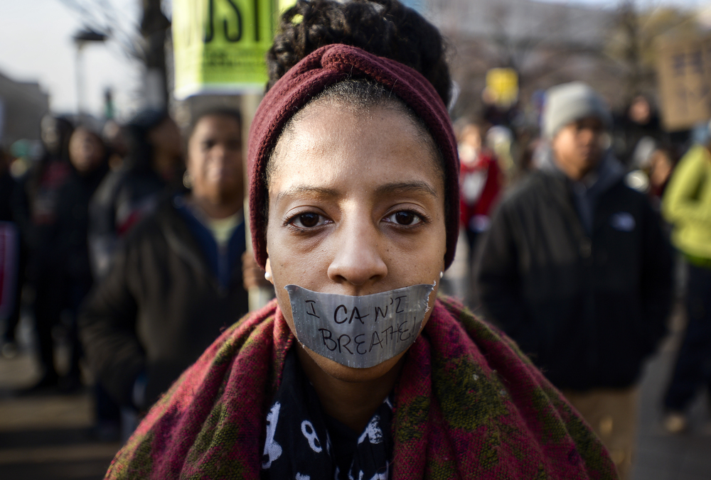 A demonstrator covers her mouth with duct tape in protest of the recent police killings in the United States. Thousands of people rallied in support of the families of Michael Brown and Eric Garner in Washington, D.C. on Dec. 13, 2014.