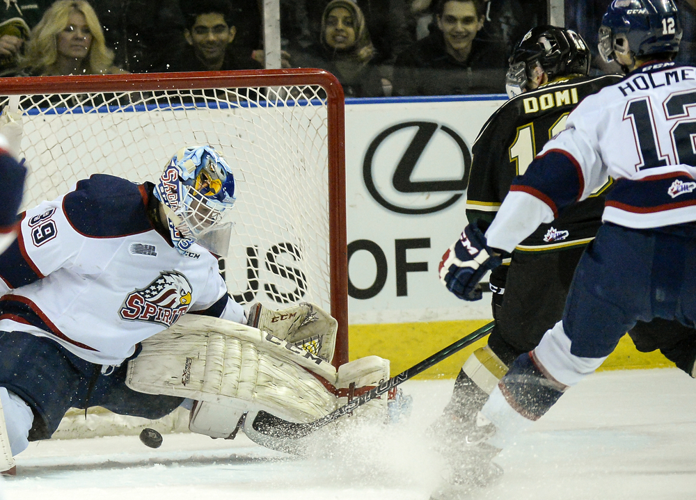 London Knights Captain Max Domi slides the puck between Saginaw Spirit goalie David Ovsjannikov in the first period at Budweiser Gardens in London, Ont. on Friday March 20, 2015. This was Domi's 100th point.