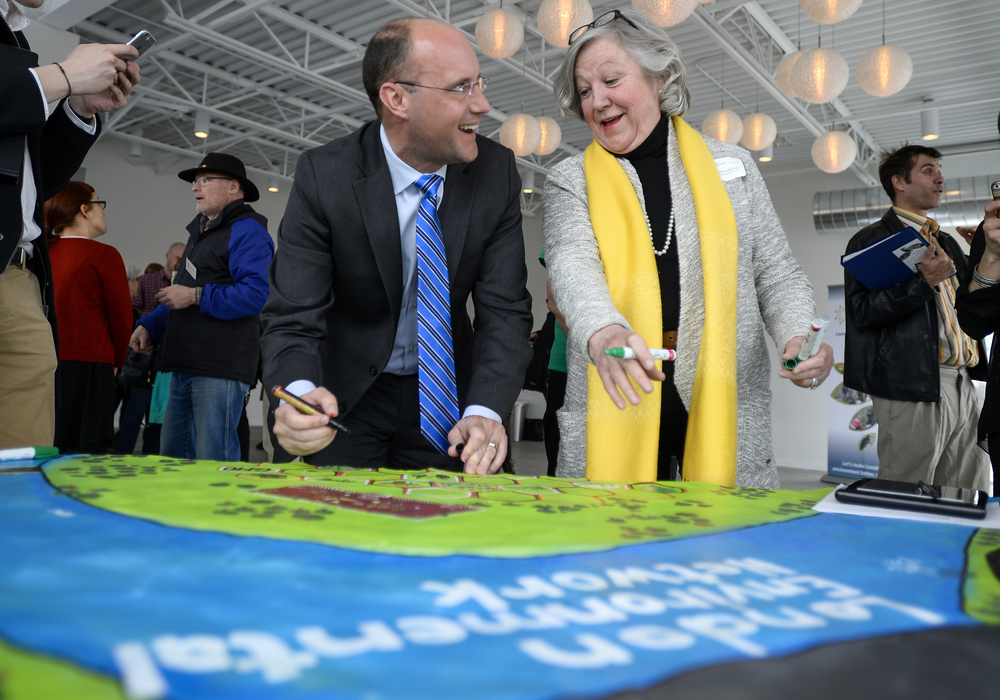 City of London Mayor Matt Brown shares a laugh with Thames Talbot Land Trust Executive Director Suzanne McDonald Aziz as they draw on a painting donated by artists Shawn Kaiser and Narcisse Datura at the London Environmental Network Launch held at Goodwill Industries in London, Ont. on Friday March 27, 2015. The London Environmental Network helps local environmental groups work better together, and has recently received a $227,700 grant from the Ontario Trillium Foundation. ANDREW LAHODYNSKYJ/ The London Free Press /QMI AGENCY