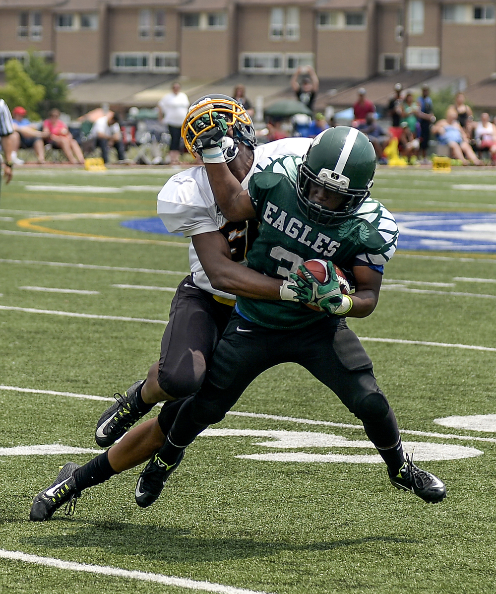 Etobicoke Eagles' Andre Atkinson gets his hand caught in the cage of a Brampton Bulldogs playing during a game at Father Henry Carr Catholic Secondary School on Sunday afternoon. The Eagles beat the Bulldogs 26-21 after a last minute touchdown in the fourth quarter.