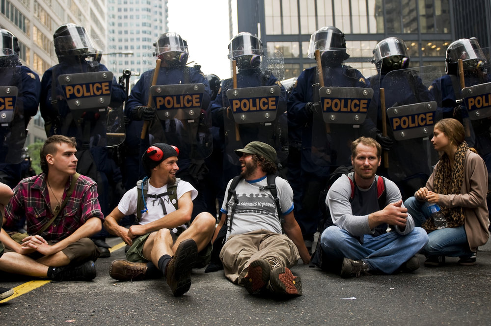 A group of protesters have a laugh as they sit in-front of a wall of riot police during Saturdays G20 protests.