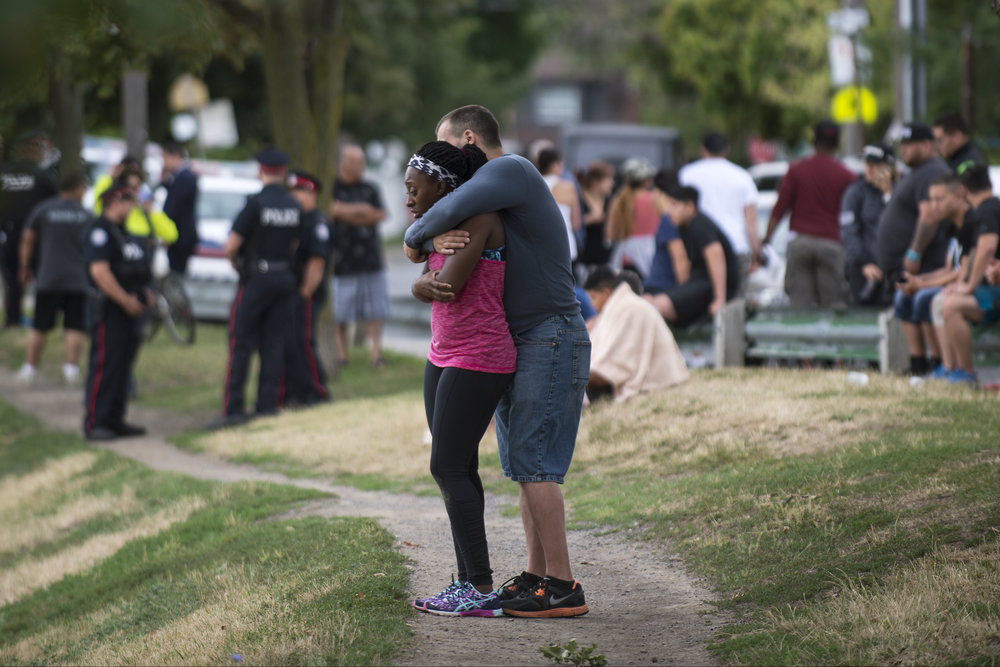 Two people comfort each other after two men were shot in Christie Pitts Park on July 30, 2016. A man in his 20's is in life-threatening condition, while the second victim, a male in his 30's, is in non-life threatening.