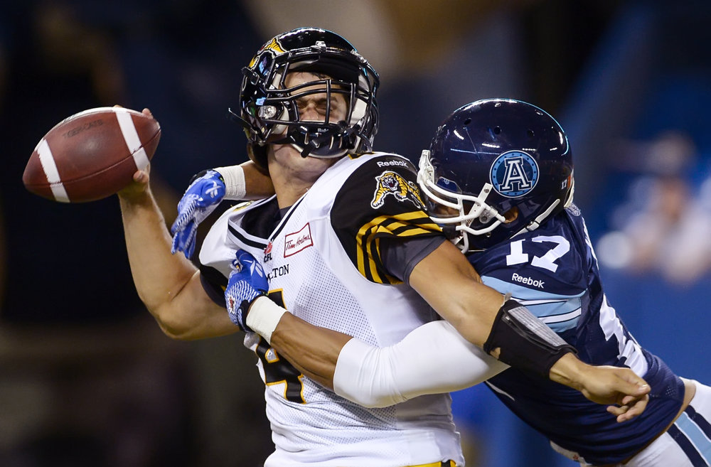 Toronto Argonauts defensive back Matt Ware sacks Hamilton Tiger-Cats quarterback Zach Collaros during second-half play at the Rogers Centre in Toronto on October 10, 2014. The Argos managed to squeak past the Ti-Cats 34-33.