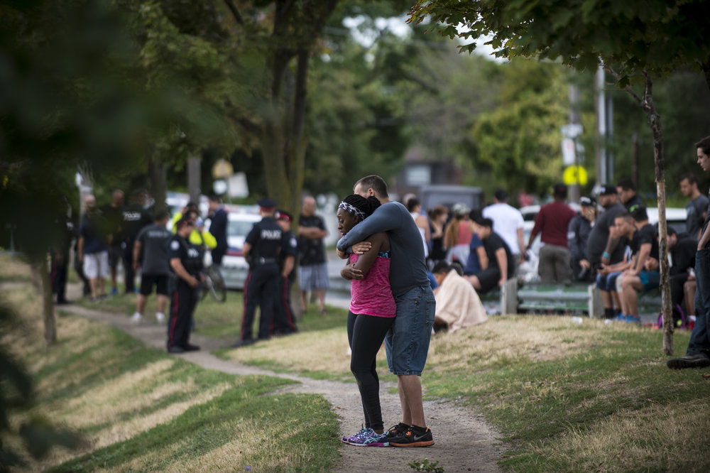 TORONTO, ON - JULY 30, 2016:  Two people comfort each other after two men were shot in Christie Pitts Park on July 30, 2016.  A man in his 20's is in life-threatening condition, while the second victim, a male in his 30's, is in non-life threatening.