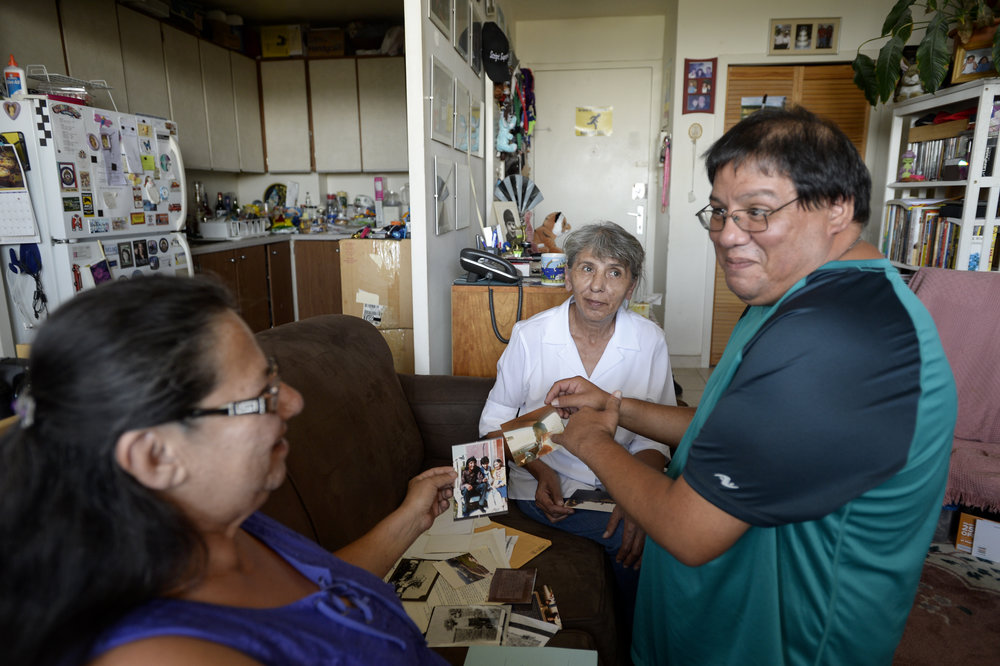 TORONTO, ON - AUGUST 24, 2016:  Karen Wahbegona (centre white shirt) looks on as her brother Thomas Norton (right), and sister Doreen Reidpath look at old documents and photos from their past inside Thomas' apartment in Toronto on  August 24, 2016. The three siblings were separated during the Sixties Scoop and have slowly been trying to reconnect with lost family.