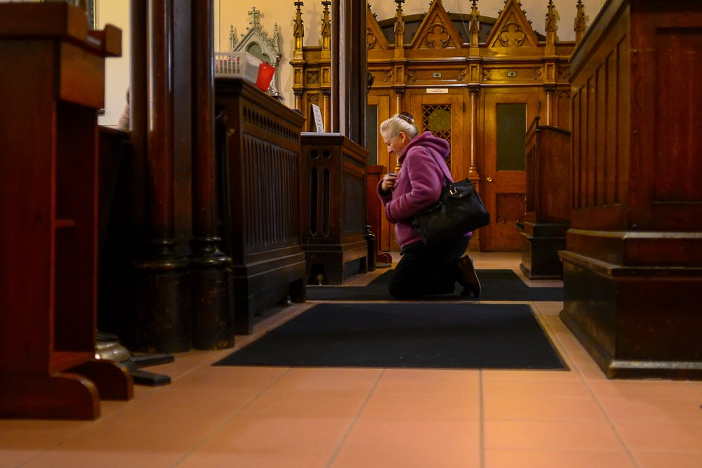 TORONTO, ON - NOVEMBER 22, 2016: A worshiper prays after entering St. Cecilia's Church during a service for the Feast of St. Cecilia on November 22, 2016.