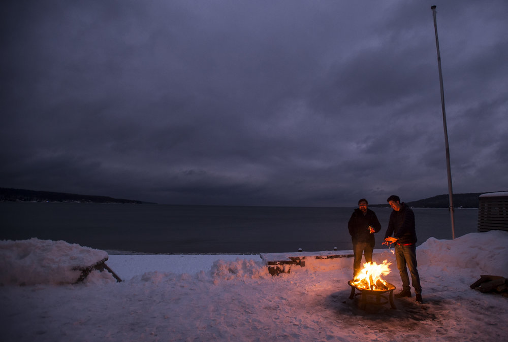 Jack Davies, left, and Brandon MacGregor keep warm at a cottage on Thunder Beach during a New Year's Eve party.