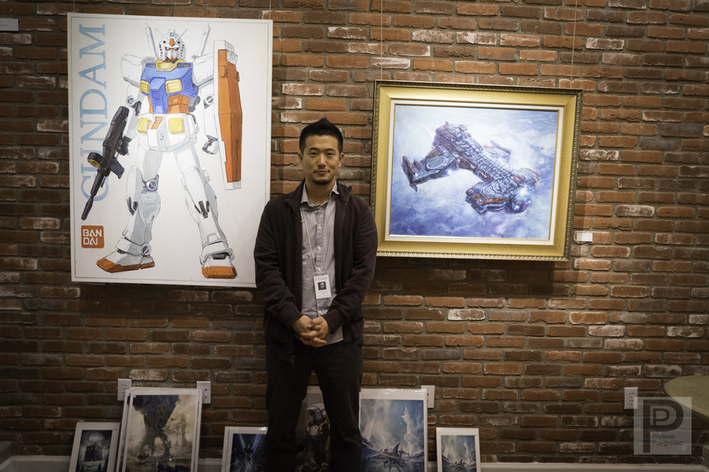 "Tae young Choi with his ""Gundam"" and ""Battlecruiser"" original art on display at the December 2015 show."