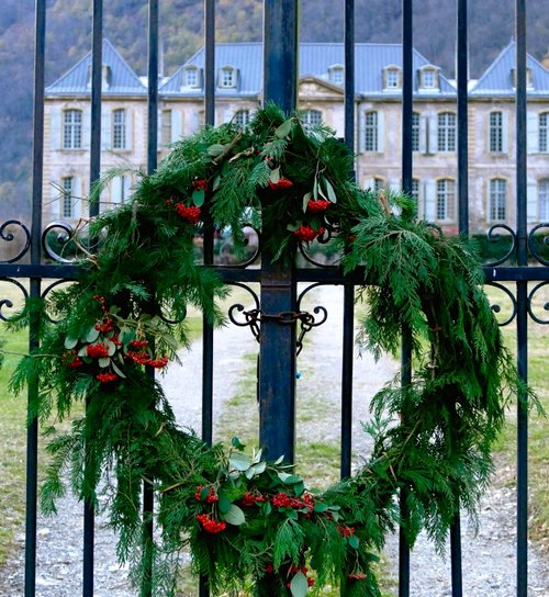 Fresh green wreath hangs on the iron gate of Chateau Gudanes. South of France Fixer Upper Château Gudanes. #southoffrance #frenchchateau #provence #frenchcountry #holidaydecor #wreath