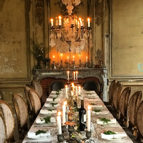 Romantic dining table with oval back dining chairs and crystal chandelier in a French chateau. South of France Fixer Upper Château Gudanes. #southoffrance #frenchchateau #provence #frenchcountry #renovation