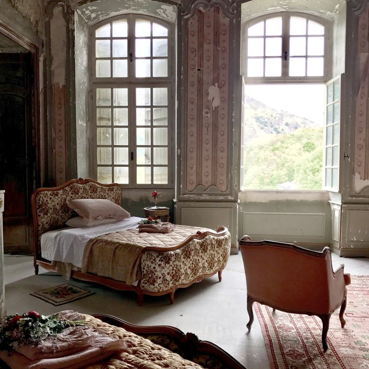 Classic French furniture in a magnificent chateau bedroom with French windows open to the mountain view. South of France Fixer Upper Château Gudanes. #southoffrance #frenchchateau #provence #frenchcountry #renovation