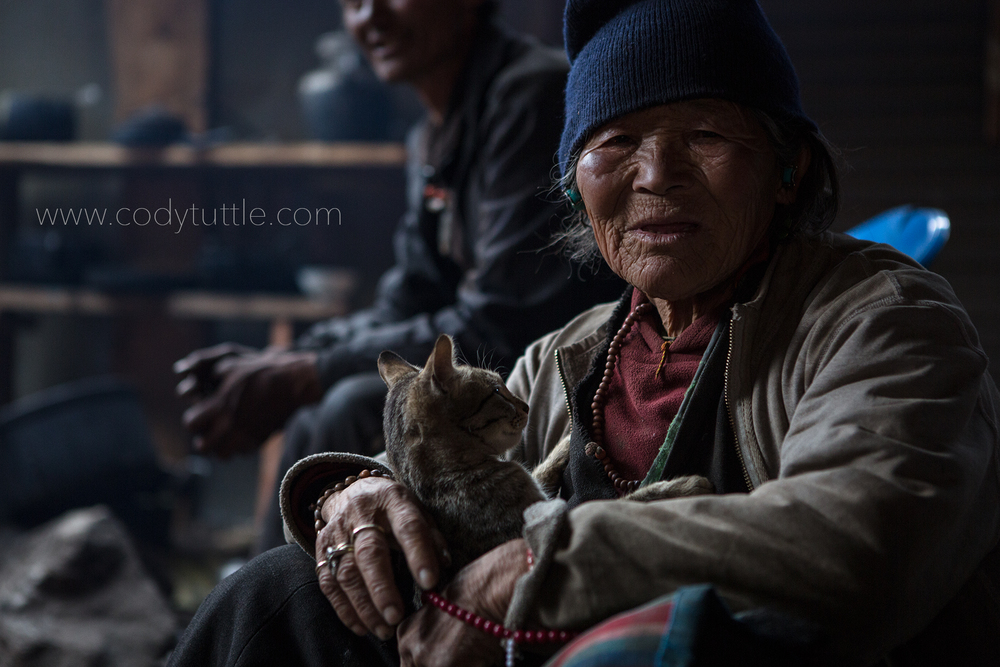 Tibetan woman relaxing with her cat in a monastery near Lho, Nepal. Photo: Cody Tuttle